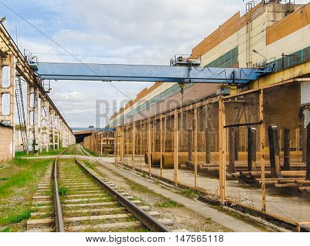Industrial area. Outdoor crane trestle. Electric overhead traveling crane above the open warehouse and loading area with the railway.