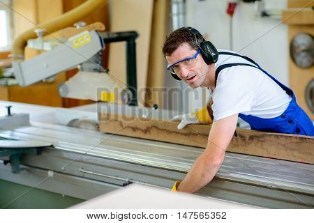 Worker In Workshop Using Saw Machine