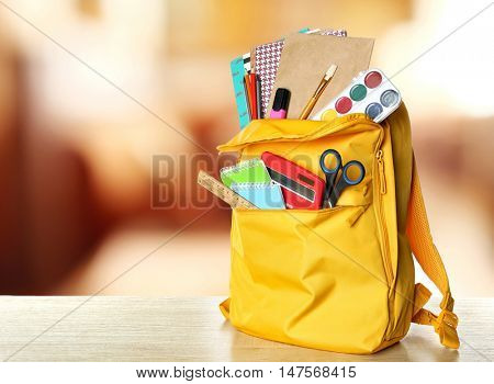 Yellow backpack with school supplies on wooden table against blurred background. School concept.