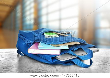 Blue backpack with school supplies on wooden table against blurred background. School concept.