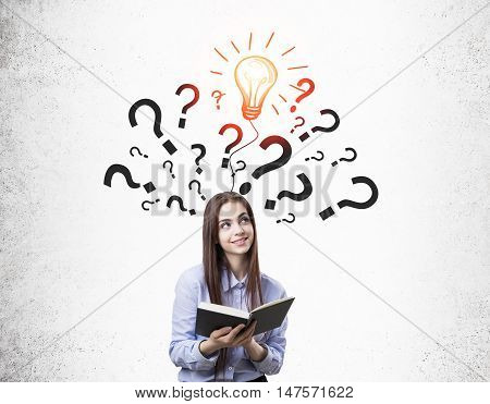 Portrait of young girl with book standing near concrete wall with question marks and light bulb sketch on it. Concept of book wizdom