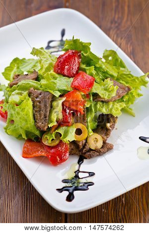 delicious fresh salad with vegetables sauce and meat on wooden  background served in cafes restaurants pizzerias snack bars  steakhouse