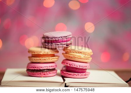 Homemade macaroons stay on open book over christmas lights. Selective focus.