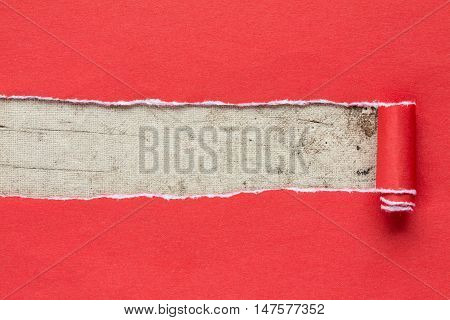 Torn red paper on dirty canvas with copy-space for text