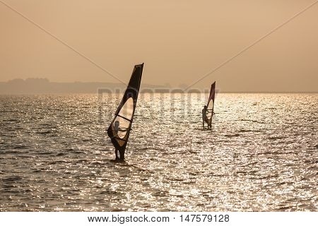 Exercising windsurfer in a sea at sunset