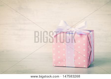 Gift box wrapped in pink dotted paper and tied satin bow over a white wood background. Vintage effect filter.