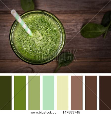 Top view of a green smoothie on an old wooden table, in a glass jar with a straw, in a colour palette with complimentary colour swatches.