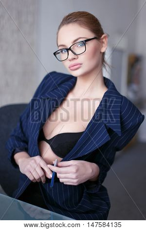 Sexy secretary in glasses undress suit in office at glass desk