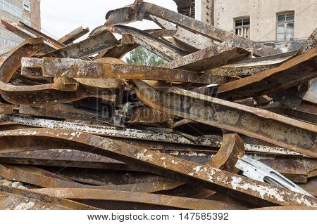 Large rusty steel beams piled up for recycling