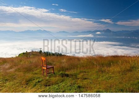 Old wooden chair on the top in Gerlitzen Apls in Austria.Inverse weather and view of the mountains in Slovenia.