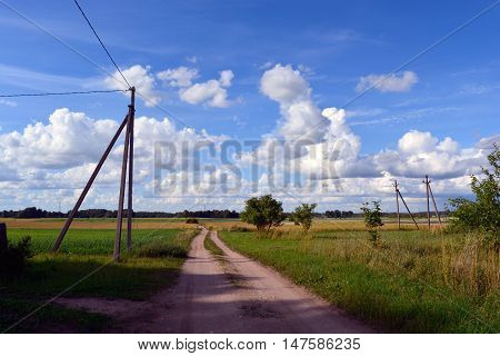 Unpaved country road through the fields on sunny cloudy summer day