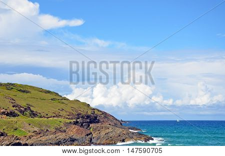Grassy, rocky coastline and aqua waters of the Pacific Ocean near Coffs Harbour on the New South Wales coast, Australia