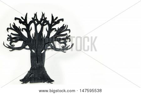 Good image for Halloween. A wooden cutout of bare tree shape painted black. The rough texture of the wood is showing through the black paint. On white background with copy space