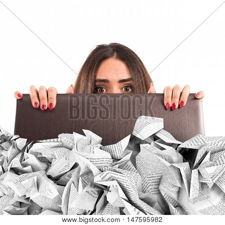 Businesswoman hidden behind the laptop screen submerged by the sheets