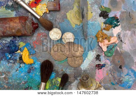 Paint brushes and vintage coins over old wooden pallet