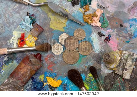 Paint brushes and old coins over old wooden pallet