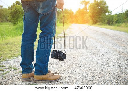 Feet Traveler man and retro photo camera outdoor Travel Lifestyle vacations and travel concept vintage tone