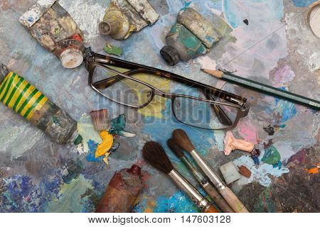 Paint brushes with glasses over old wooden pallet