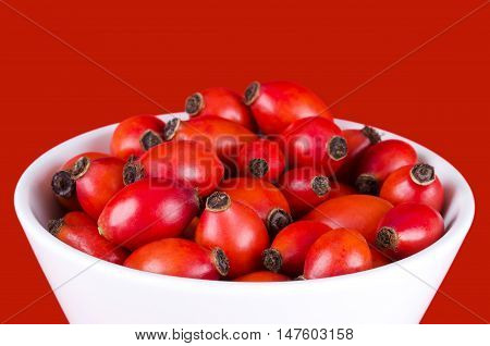 Rose hips in white bowl over red, also rose haw or rose hep. Ripe red fruits of roses, used for herbal teas, jam and they can be eaten raw. One of the richest vitamin C sources available in plants.
