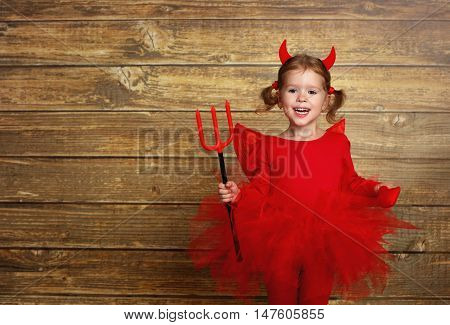 funny child girl in devil halloween costume with horns and trident on a dark wooden background