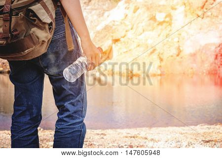 Hipster man holding bottle of water at summer river