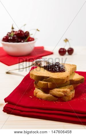 Rusk with cherry jam over a red napkin and cherry fruit on background