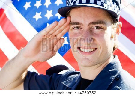 young american policeman saluting, background is USA flag