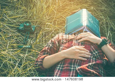 hipster man lying down on grassland napping tired after reading book with nature around outside poster