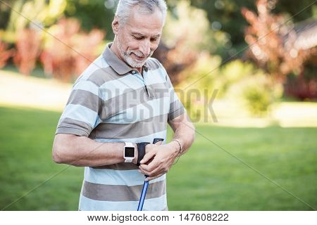 Little break. Grandfather having a pause while jogging in summer park