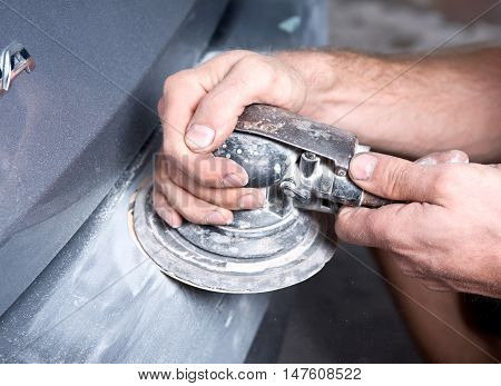 Worker is sanding filler with air sander in auto body shop