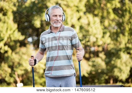 Happy walk. Grey-haired man with huge ear-phones exercising during a sunny day in summer