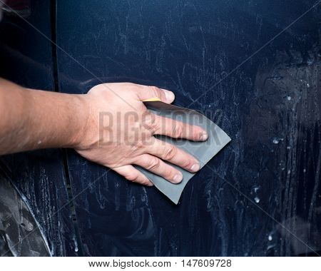 Worker hand sanding auto body preparing for buffing