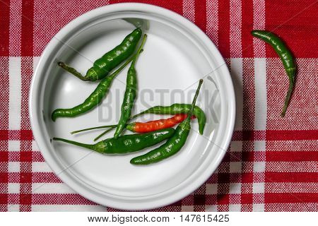Chili peppers inside bowl on red table cloth