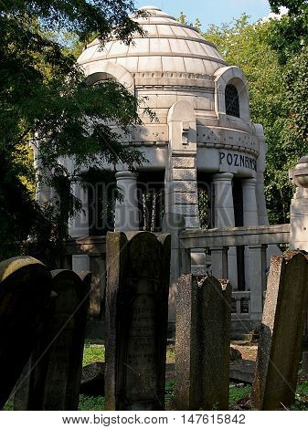 Mali in the shadow of the great. Lodz, Poland September 11, 2016 Modest Jewish gravestones on the background of the magnificent mausoleum of the family of Israel Poznanski's historic Jewish cemetery in Lodz.