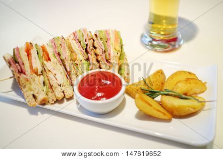 Sandwiches with ham, red sauce and and fried potatoes on plate on table