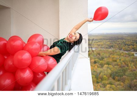 Happy woman in green dress holds many red balloons and throws away one on balcony