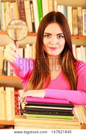 Investigation exploration education concept. Closeup intelligent student girl in library woman holding magnifying glass loupe
