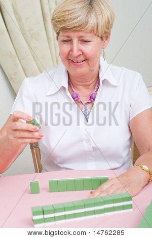 happy senior playing mah-jong game