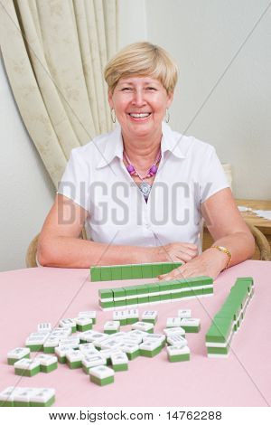 cheerful elderly lady playing mah-jong game