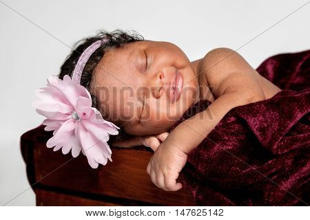 A sweet African American baby sleeps in a wooden box. She has a small smile on her lips.