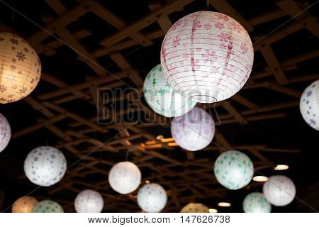 Many white round Chinese paper lanterns hanging in the darkness. Varicolored lamps lighting at night