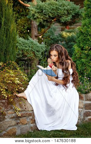 Lovely girl with enthusiasm reads the interesting book. She holding a book and an apple in his hand.