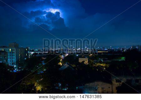Bangkok Thailand - September 0162016 : Storm clouds with lightning strike bolts passing over night city of Bangkok cityscape.