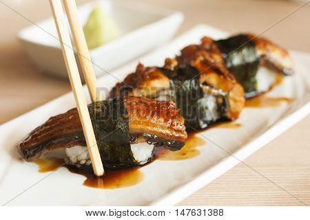 Unagi sushi nigiri in chopsticks , Japanese food