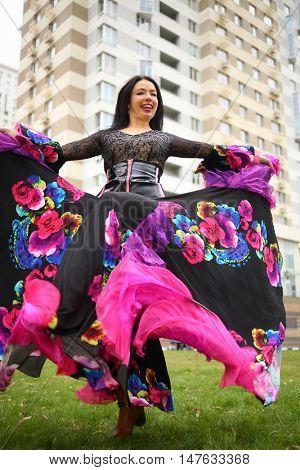 Young woman in beautiful skirt zingara dances on lawn near building