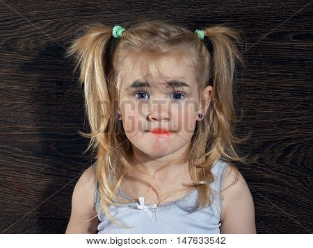Funny little girl with unskillful make-up on her face