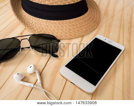 Travel accessories concept. Smartphone earbuds sunglasses woven hat on wooden table.