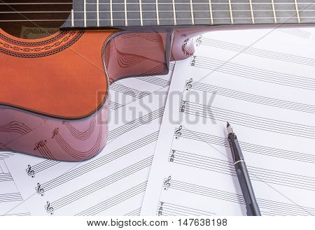 Acoustic guitar, music paper and fountain pen on wooden table