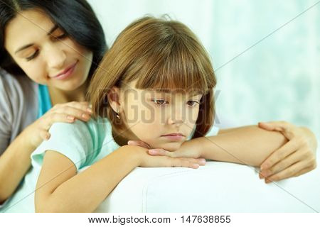 Little sulky girl being sad, and her mother consoling her