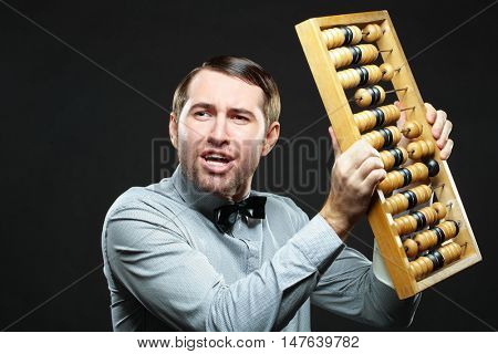 Aggravated businessman holding an old fashioned abacus on black background